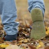Shoes walking on autumn leaves from rear