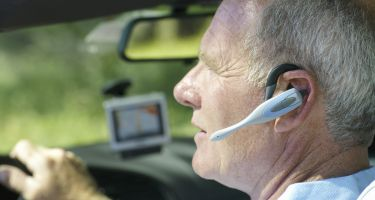 Man with hands-free device in car, side view