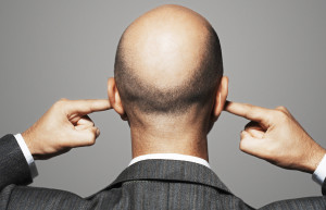 Rear View Of Bald Businessman With Fingers In Ears