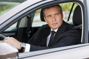 Driving his new car. Confident mature businessman driving car and looking away